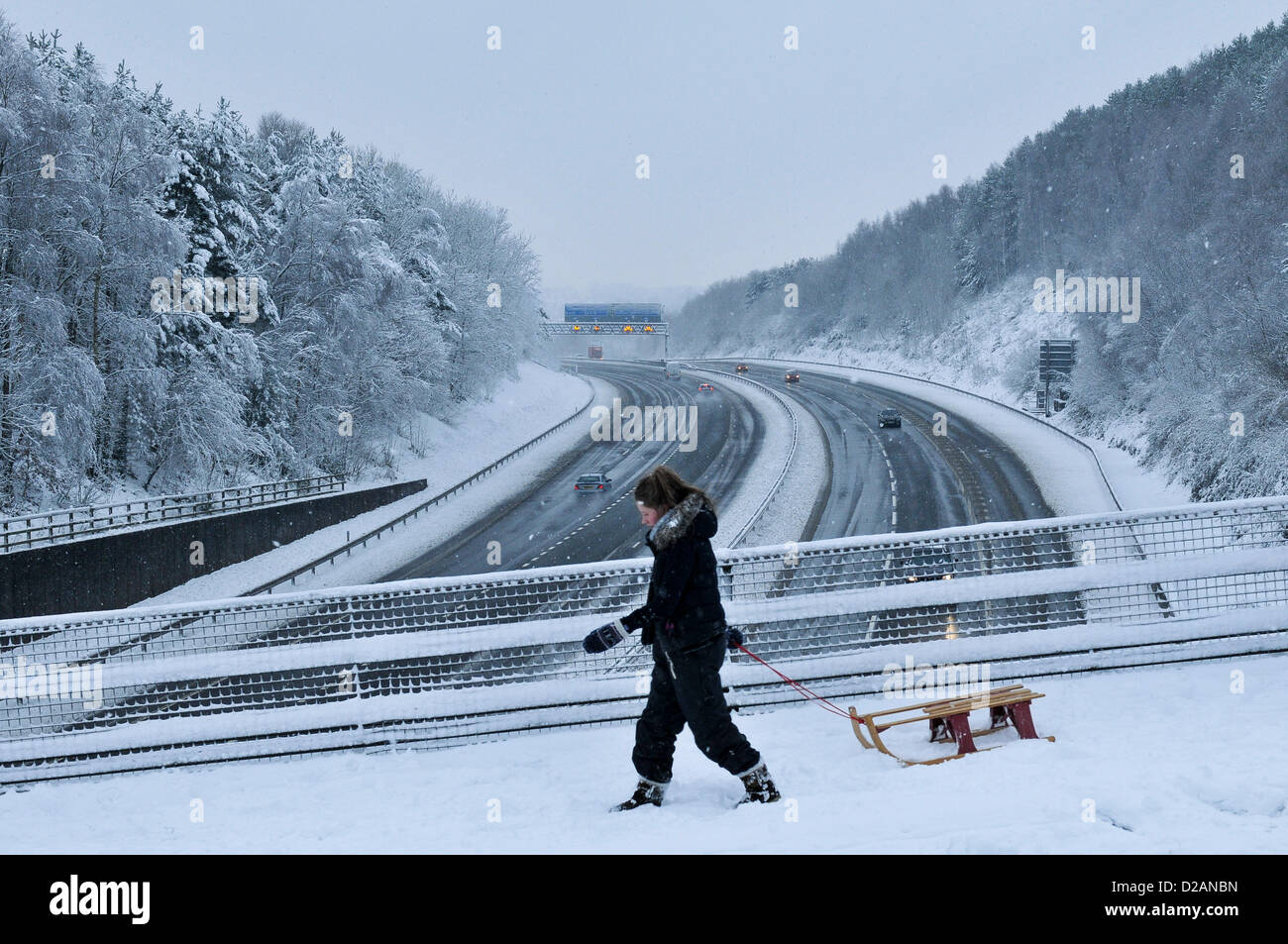 M4 Motorway. Cardiff, UK. Friday 18th January 2013. A woman pulls her sledge across a bridge over the M4 Motorway - Stock Image