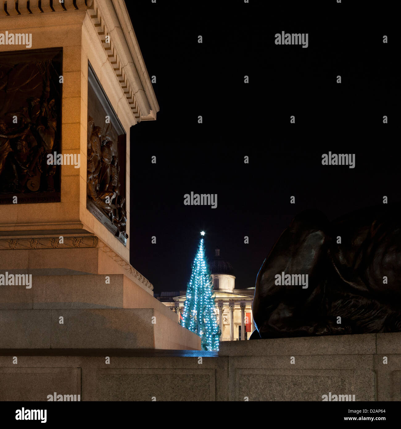 Christmas tree lit up in city square - Stock Image