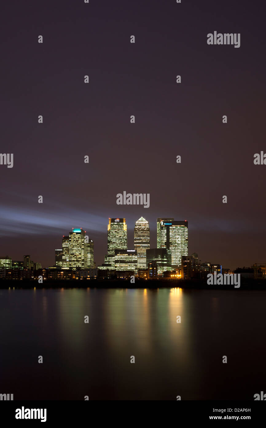 Urban skyscrapers lit up at night - Stock Image