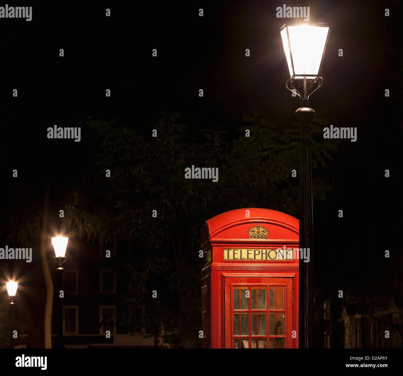 Red telephone box on city street - Stock Image