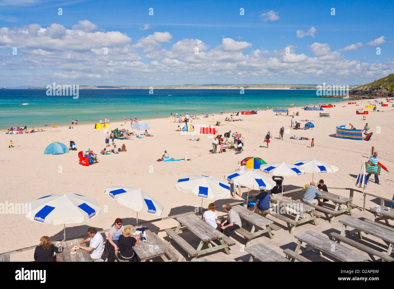 holidaymakers sunbathing and enjoying themselves on Porthmeor beach and cafe  St Ives Cornwall England UK GB EU - Stock Image