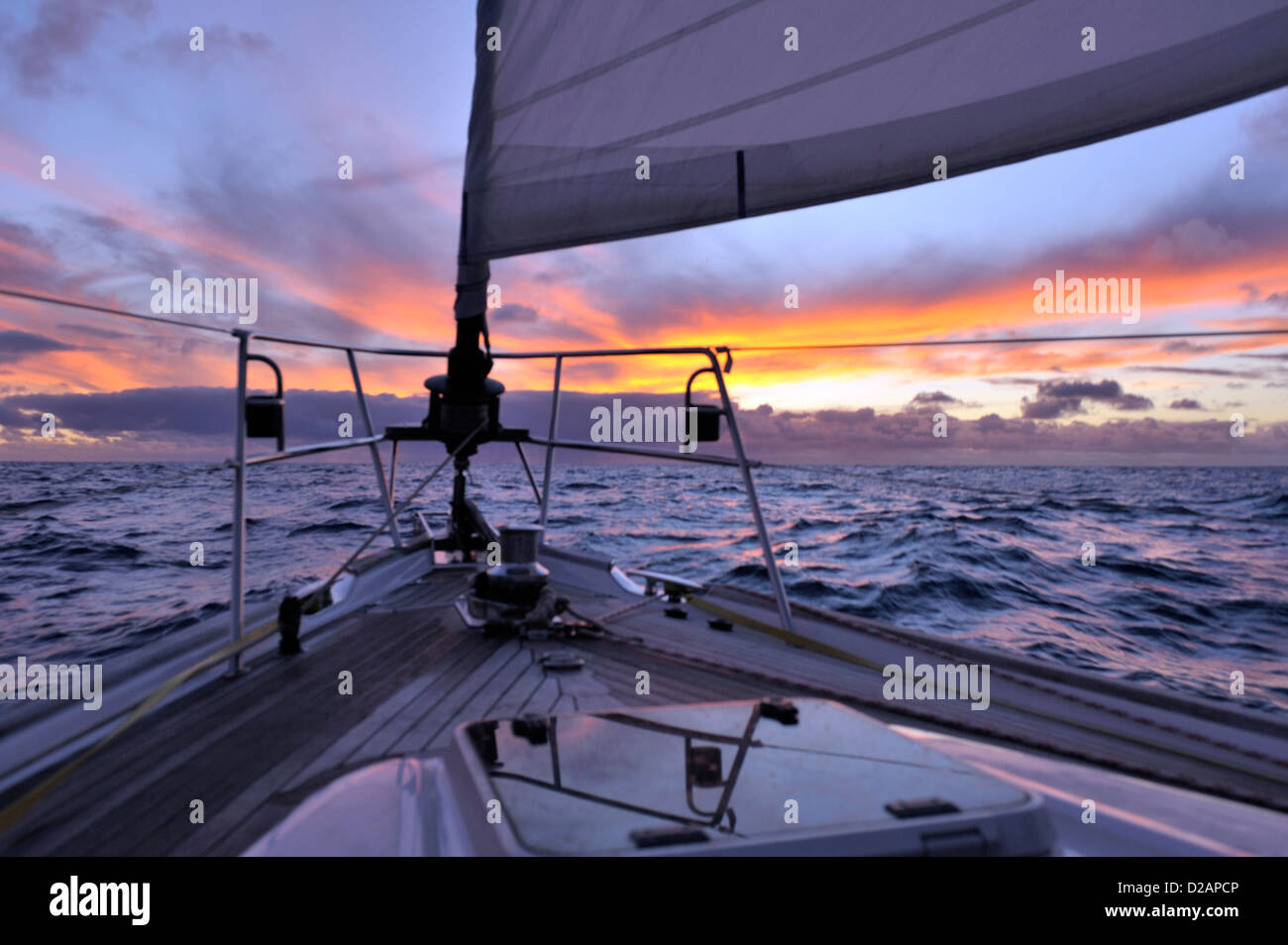 Squall ahead on the horizon at sunset seen over the bow of a cruising yacht sailing offshore into the sunset from - Stock Image