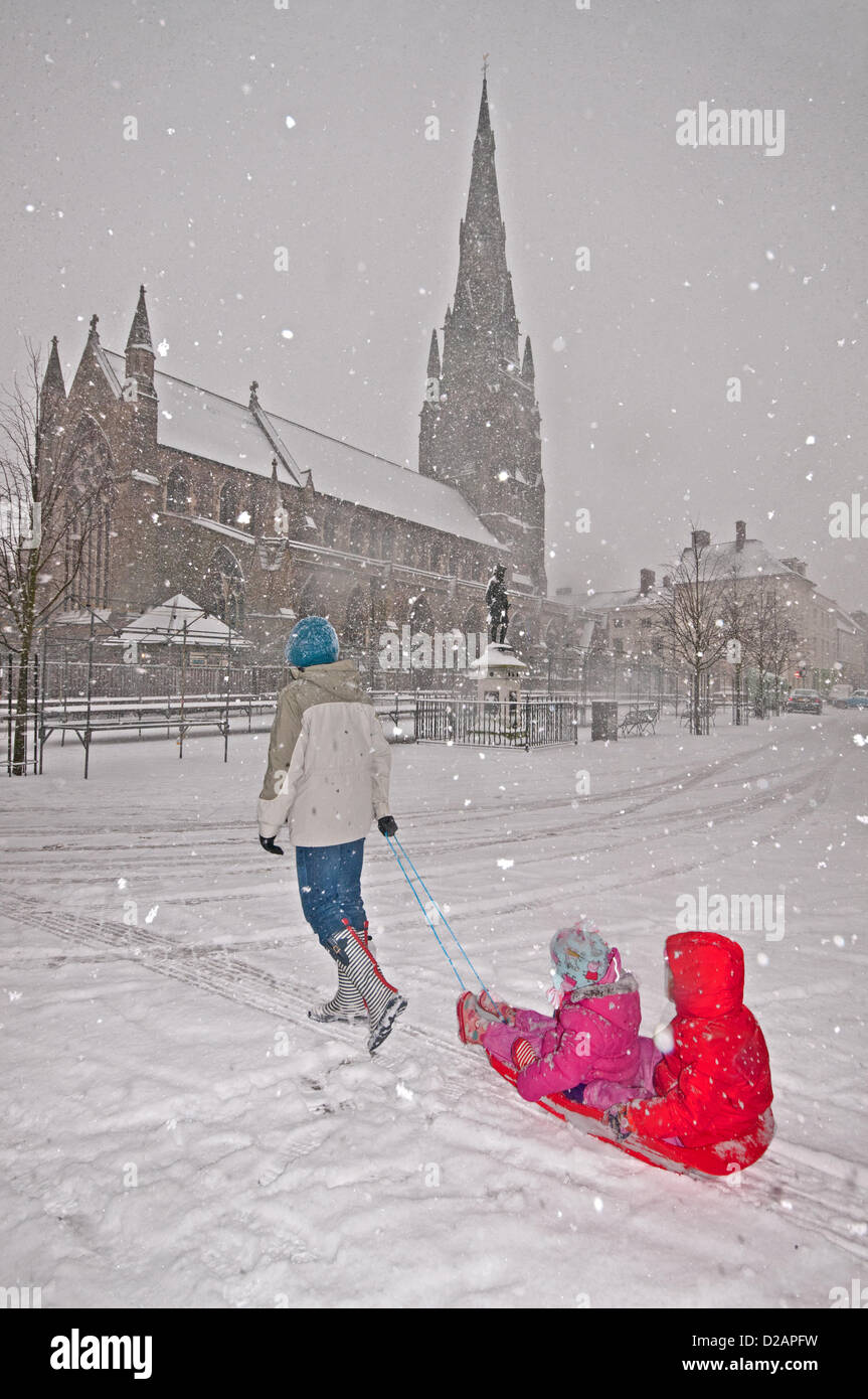 Young mother Joanne Grumett tows a sledge with her two young girls to enjoy the snow in blizzard conditions in the Stock Photo