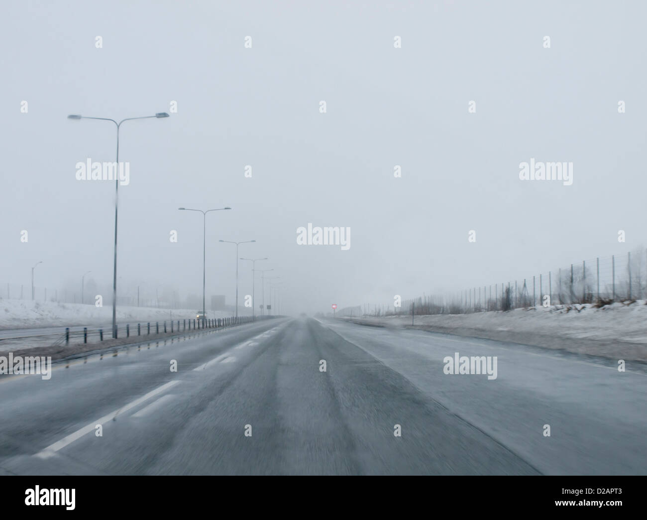 low visibility, poor driving conditions, sleet, fog and snow on the highway, typical winter scenery in Norway - Stock Image