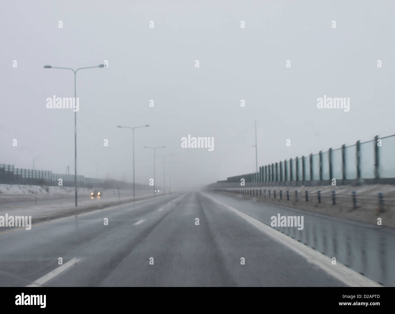 low visibility, poor driving conditions, sleet, fog and snow on the highway, typical winter conditions in Norway - Stock Image