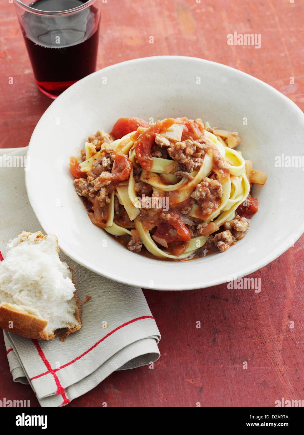 Bowl of fettuccine bolognese with bread - Stock Image