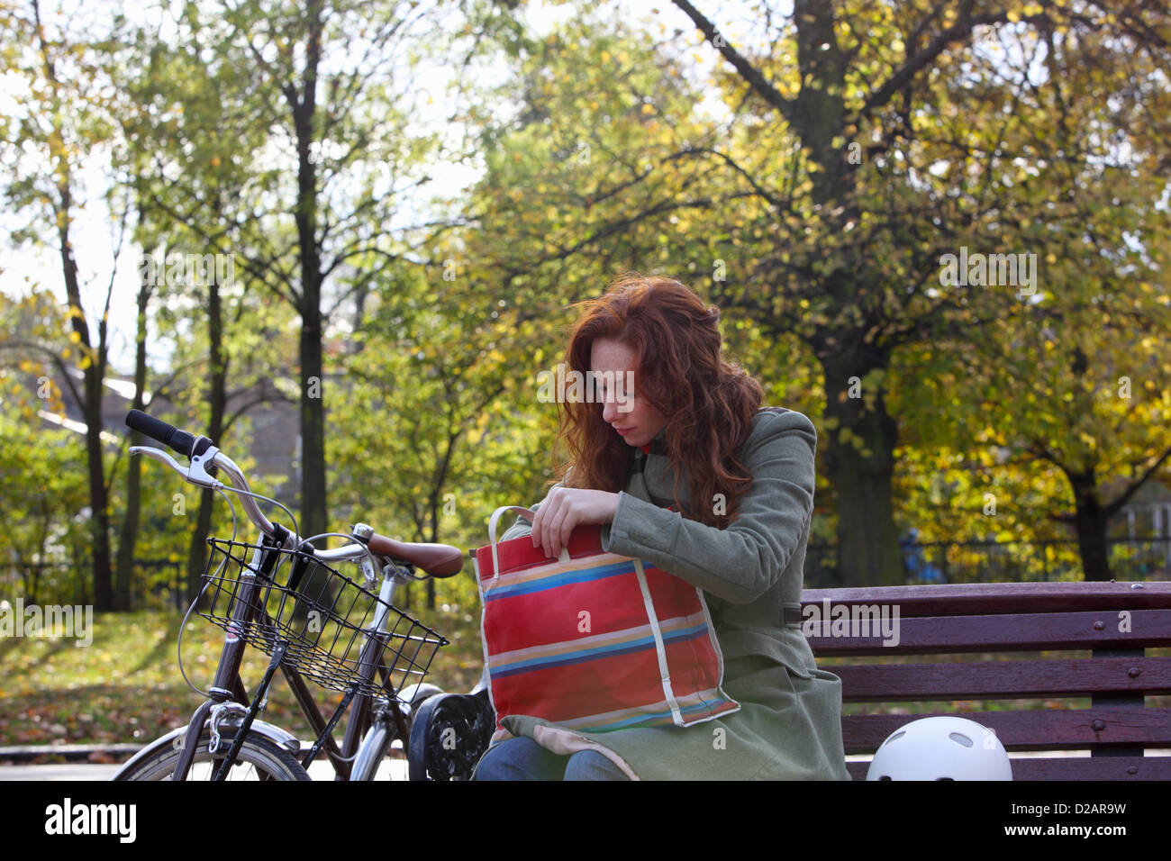 Woman looking through bag on bench - Stock Image