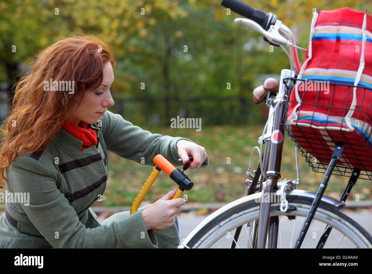 Woman locking up bicycle in park - Stock Image