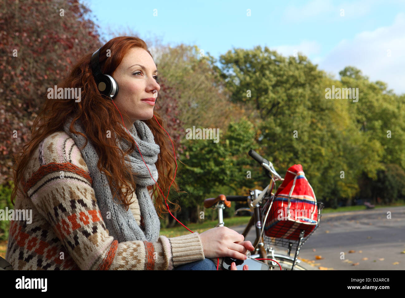 Woman listening to headphones in park - Stock Image