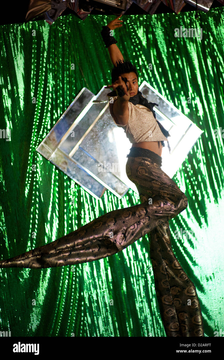 Acrobatic Stilt Walker Dancing In A Shadow And Light Green Circus Curtain