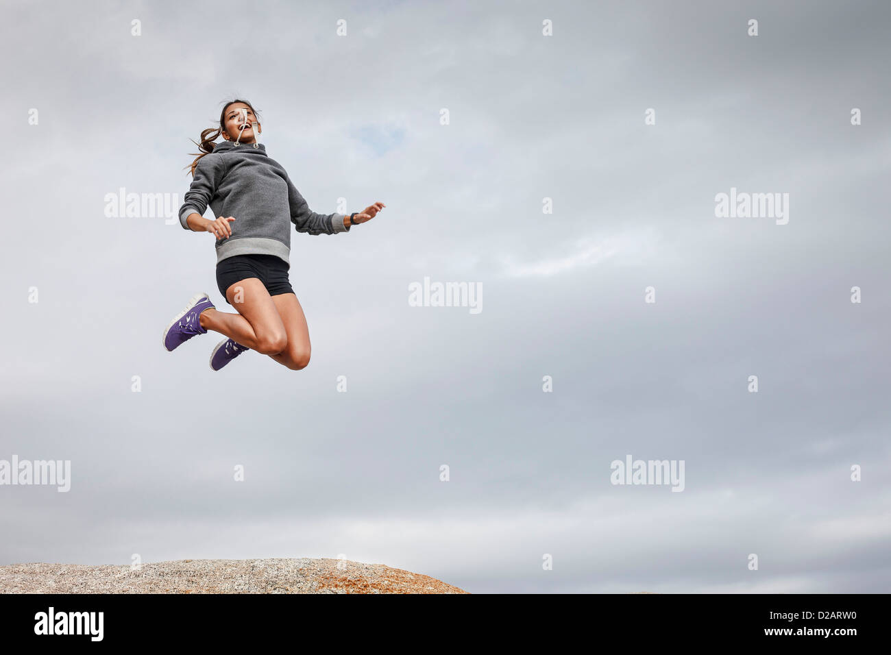 Woman jumping for joy on boulder - Stock Image