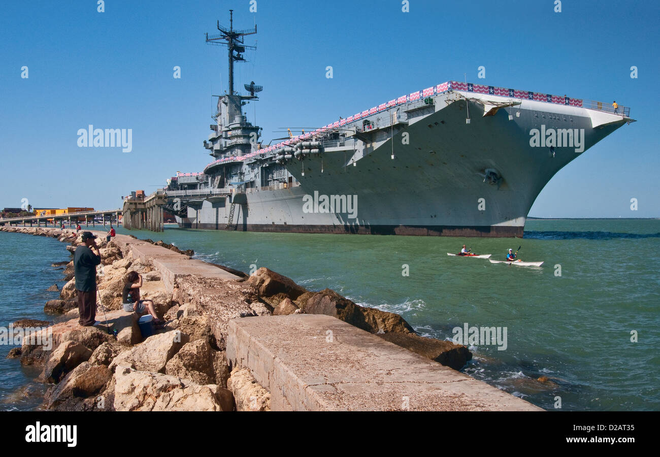 Kayakers passing WW2 aircraft carrier, anglers at pier, USS Lexington Museum on the Bay, Corpus Christi, Gulf Coast, - Stock Image