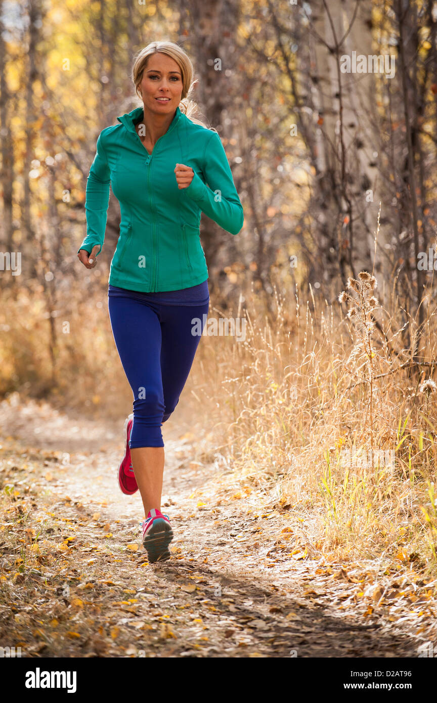 Woman jogging on dirt path - Stock Image