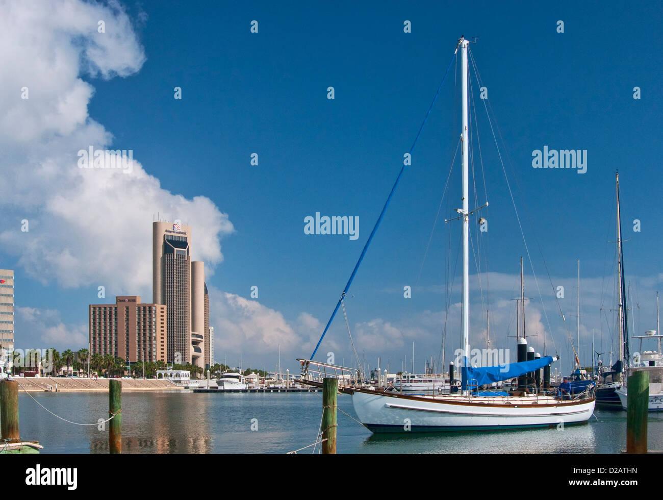 Pleasure boat at Lawrence Street T-Head pier marina, downtown towers behind at Corpus Christi Bay, Corpus Christi, - Stock Image