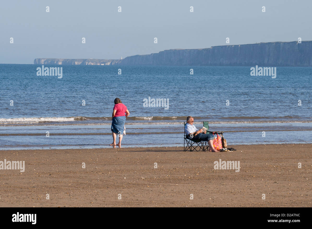 Holiday couple on quiet sandy beach (paddling sitting relaxing in sun) by calm blue flat sea - South Bay, Scarborough, Stock Photo