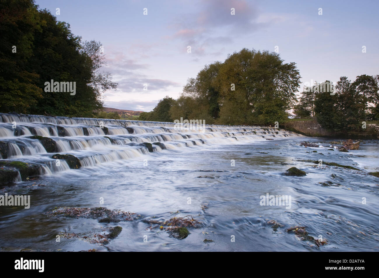 Scenic, evening, rural landscape of water flowing & tumbling over & down weir steps - River Wharfe, Burley - Stock Image
