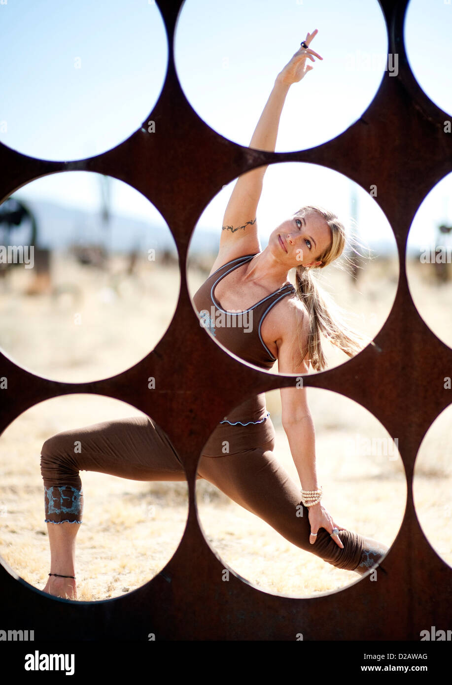 Woman in yoga pose behind a screen of circles. - Stock Image