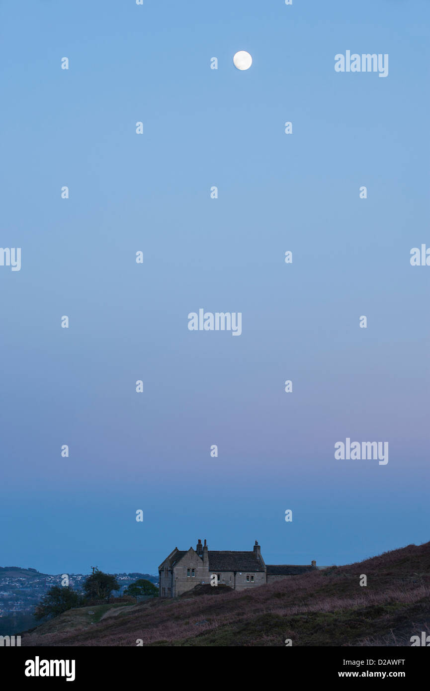Full Moon at dusk, high in a blue sky over over a stone-built house on heather moorland - above Burley-in-Wharfedale, - Stock Image