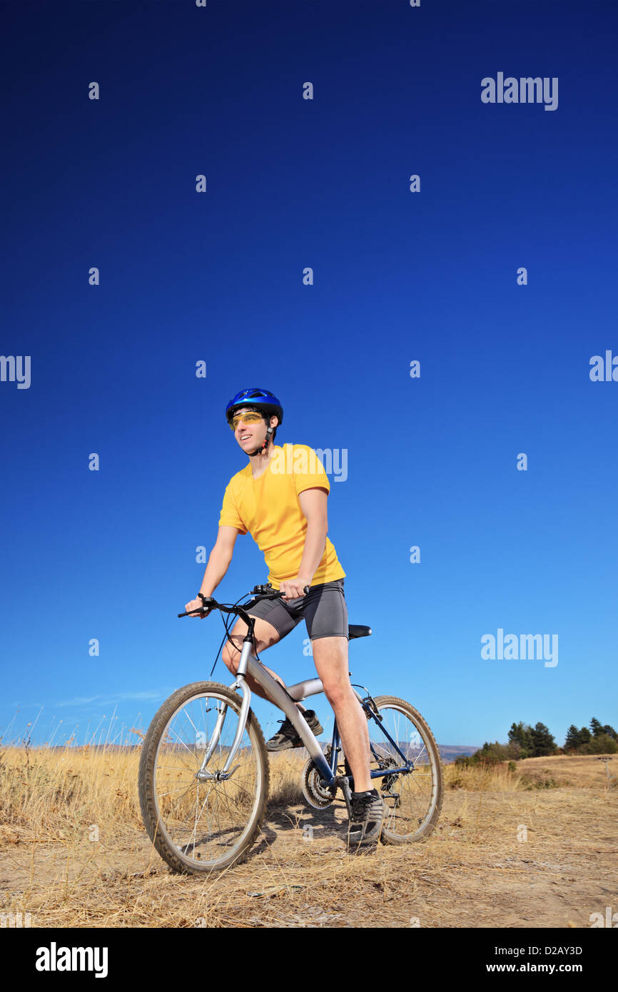 Panning shot of a bicycle rider riding a bike outdoors on a sunny day against a blue sky - Stock Image