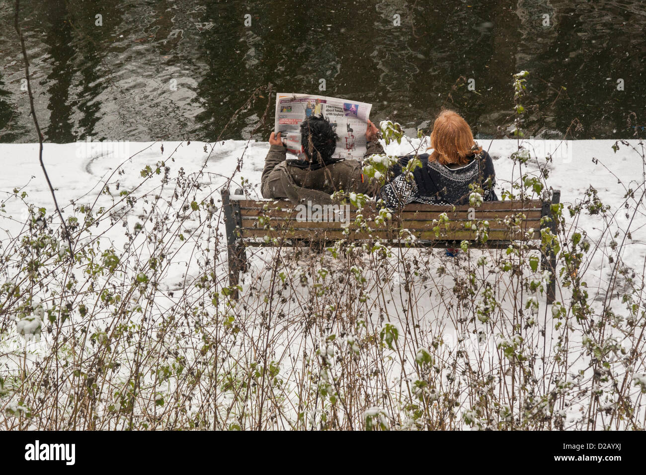 London, UK. 18th January 2013. chilling out on a bench along the Regent's Canal, Central London, as snow falls - Stock Image