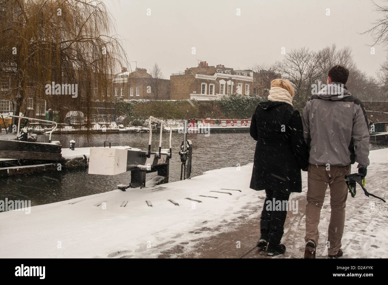 London, UK. 18th January 2013. Couple stroll along Regent's Canal, Central London, as snow falls across the - Stock Image