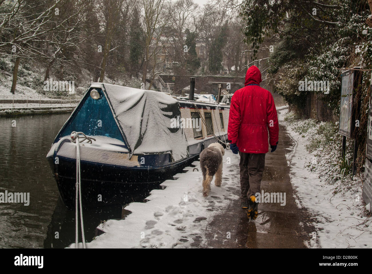 London, UK. 18th January 2013. Man strolls along the Regent's Canal, Central London, as snow falls across the - Stock Image