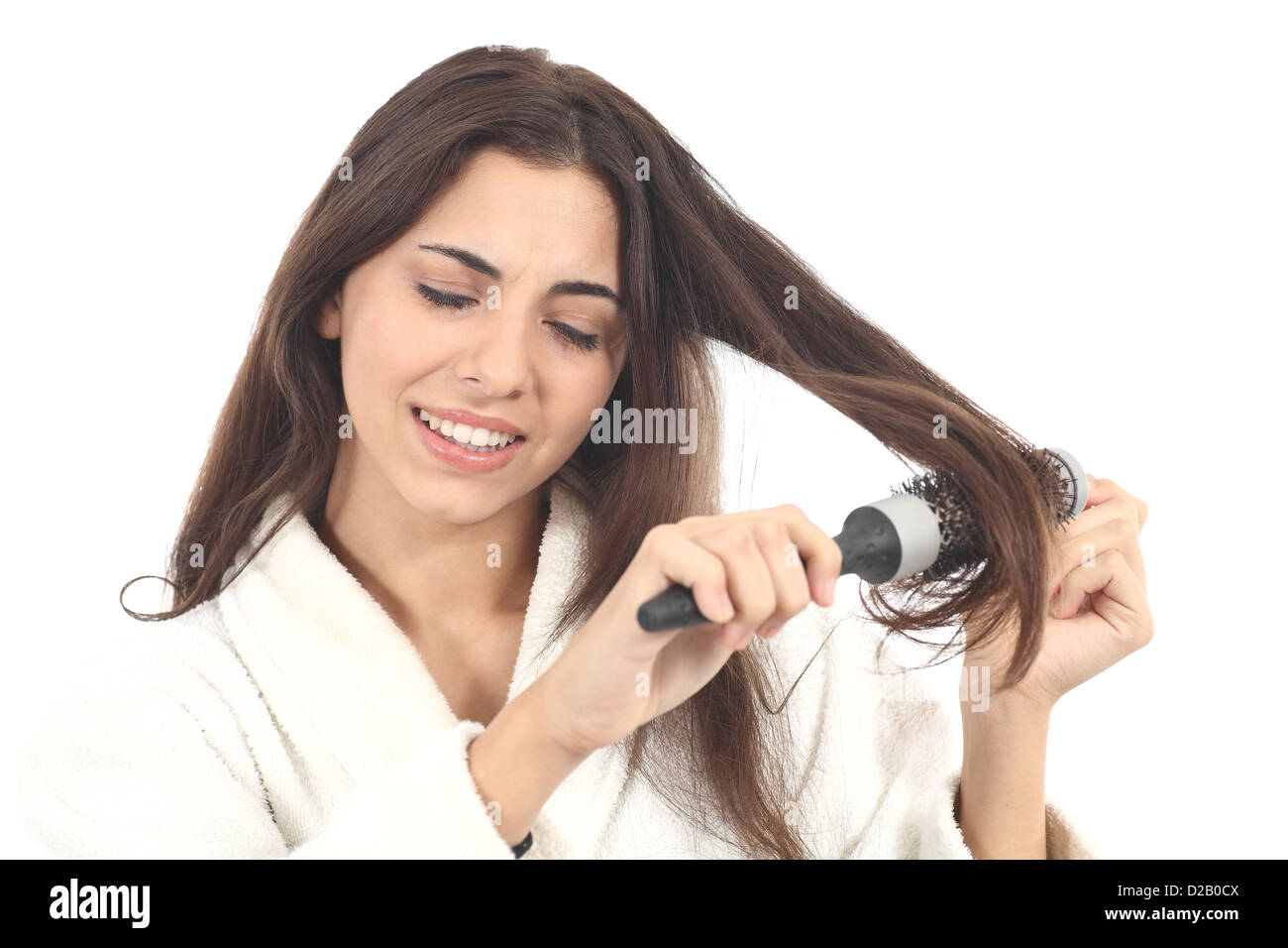 Woman suffering combing with the hairbrush on a white isolated background - Stock Image