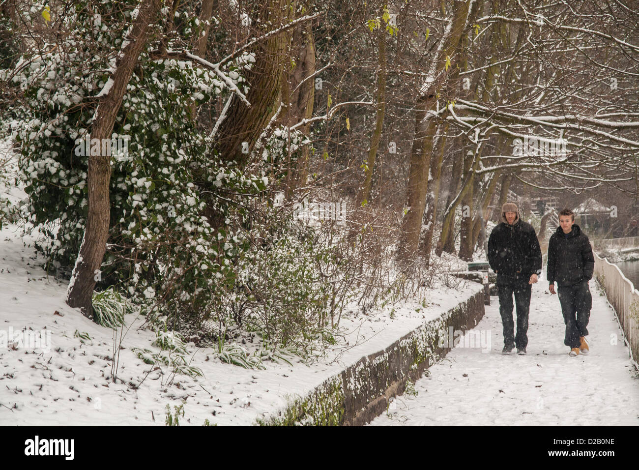 London, UK. 18th January 2013. Strolling along Regent's Canal, Central London, as snow falls across the South - Stock Image