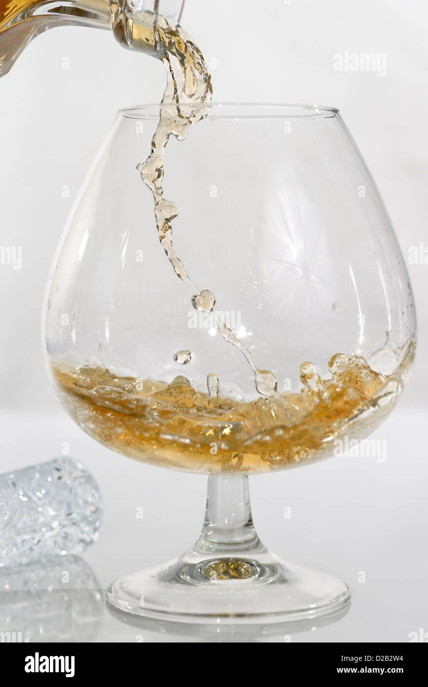 High speed photo of liquor pouring into a brandy snifter on white background Stock Photo