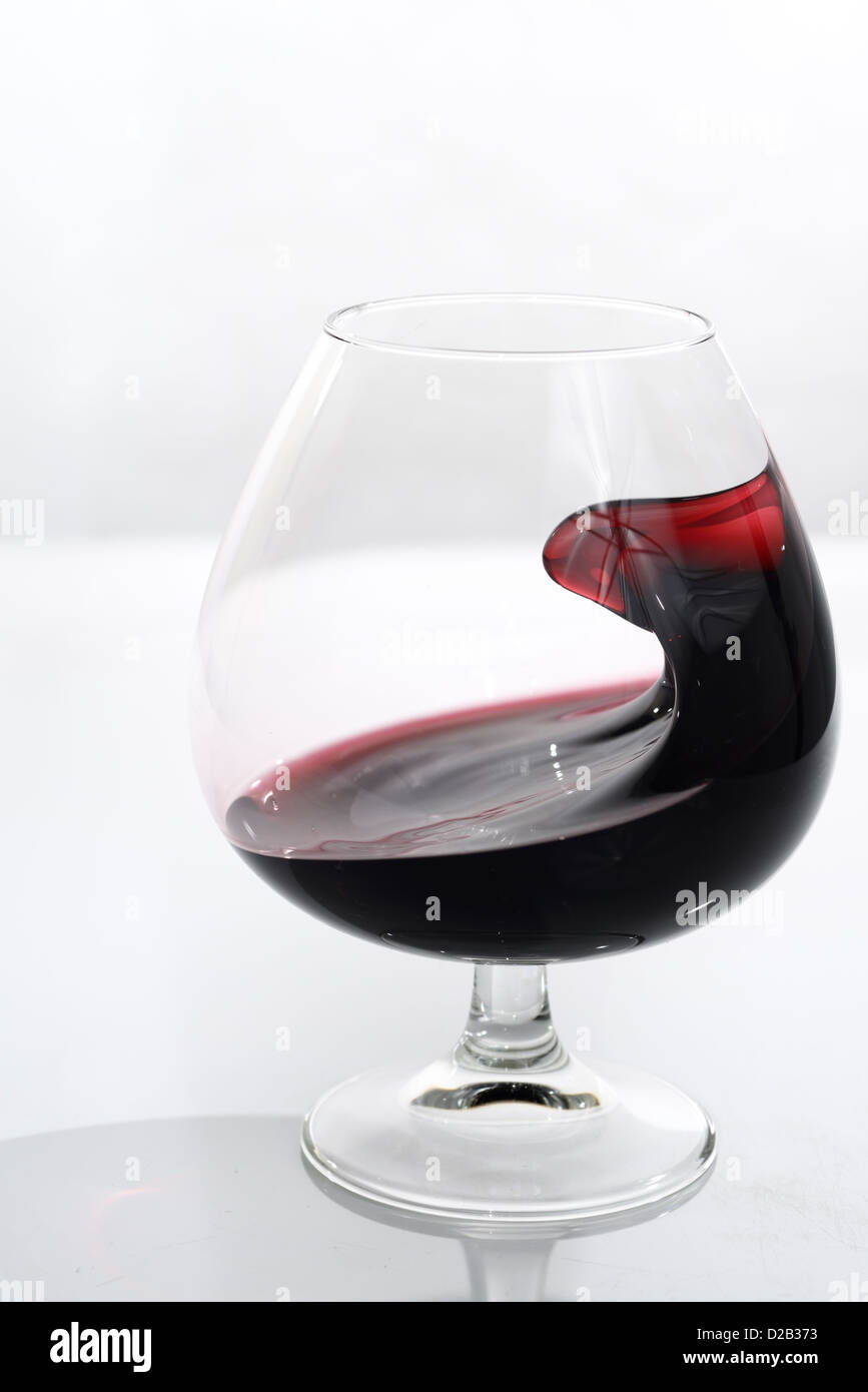 Odd shape of port swirling in a glass snifter on white background - Stock Image
