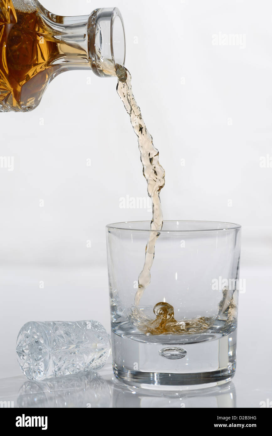 Pouring Whiskey from a crystal decanter into a tumbler glass on white background - Stock Image