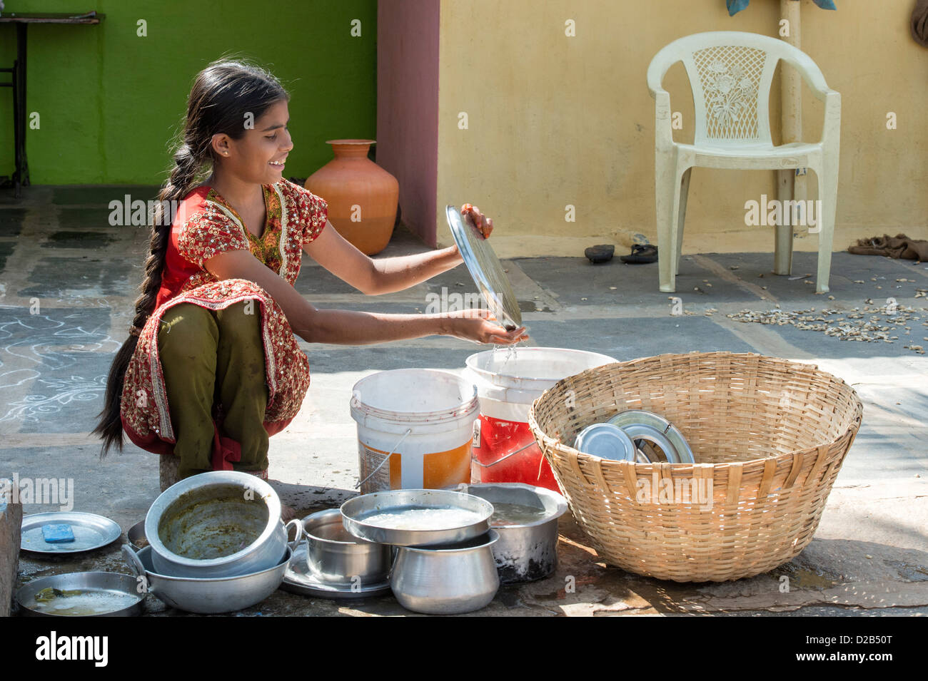 Teenage Indian girl washing dishes outside her rural indian village home. Andhra Pradesh, India - Stock Image