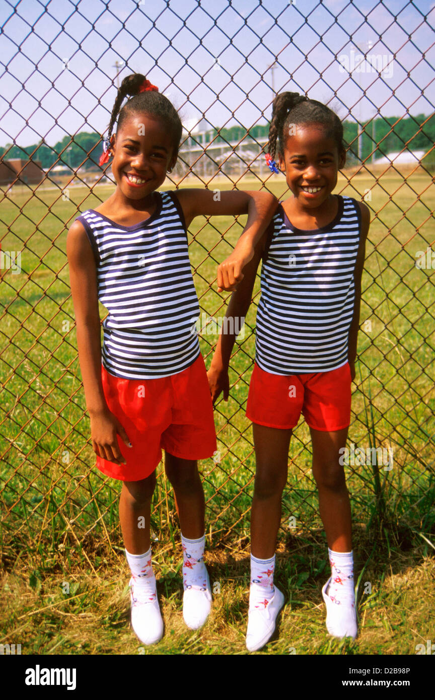 Twins, Around Ten Years Old, Pose In Matching Shirts And Shorts - Stock Image