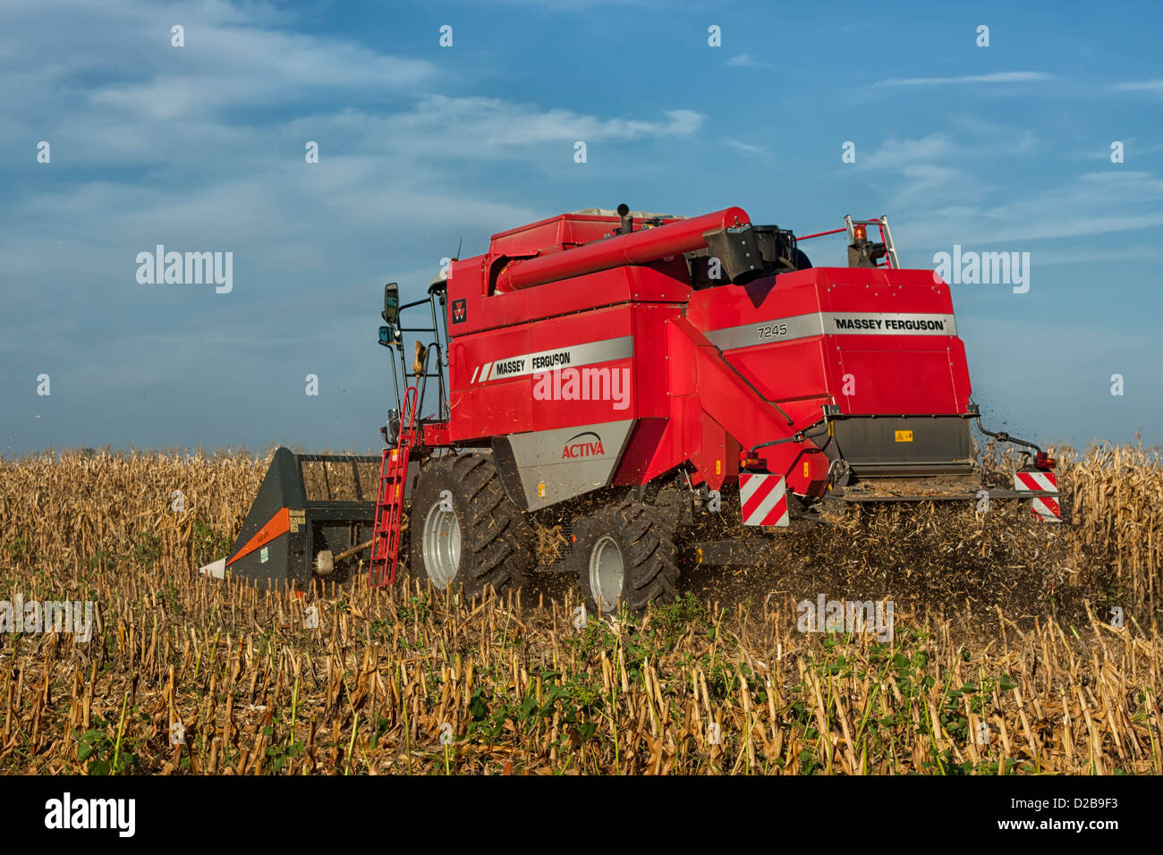 Combined harvester harvesting a crop of maize in a rural environment - Stock Image