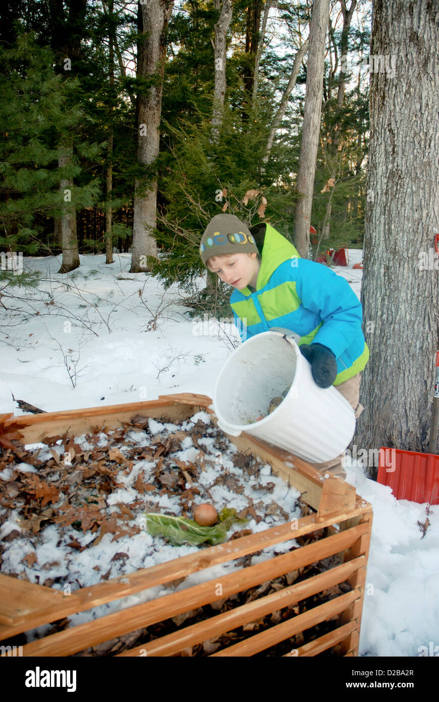 5 Year Old And 8 Year Old Girls Dumping Food Scraps Into Compost Bin - Stock Image