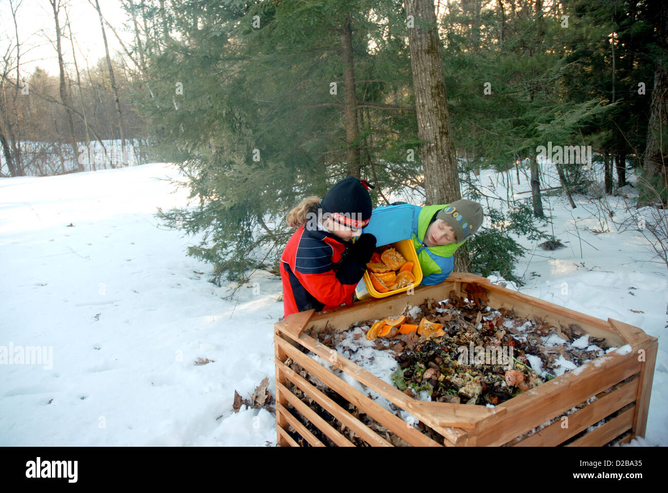 Girl Dumping Food Scraps Into Compost Bin - Stock Image