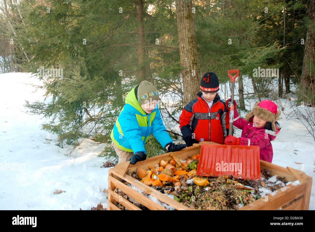 Girls Dumping Food Scraps Into Compost Bin - Stock Image