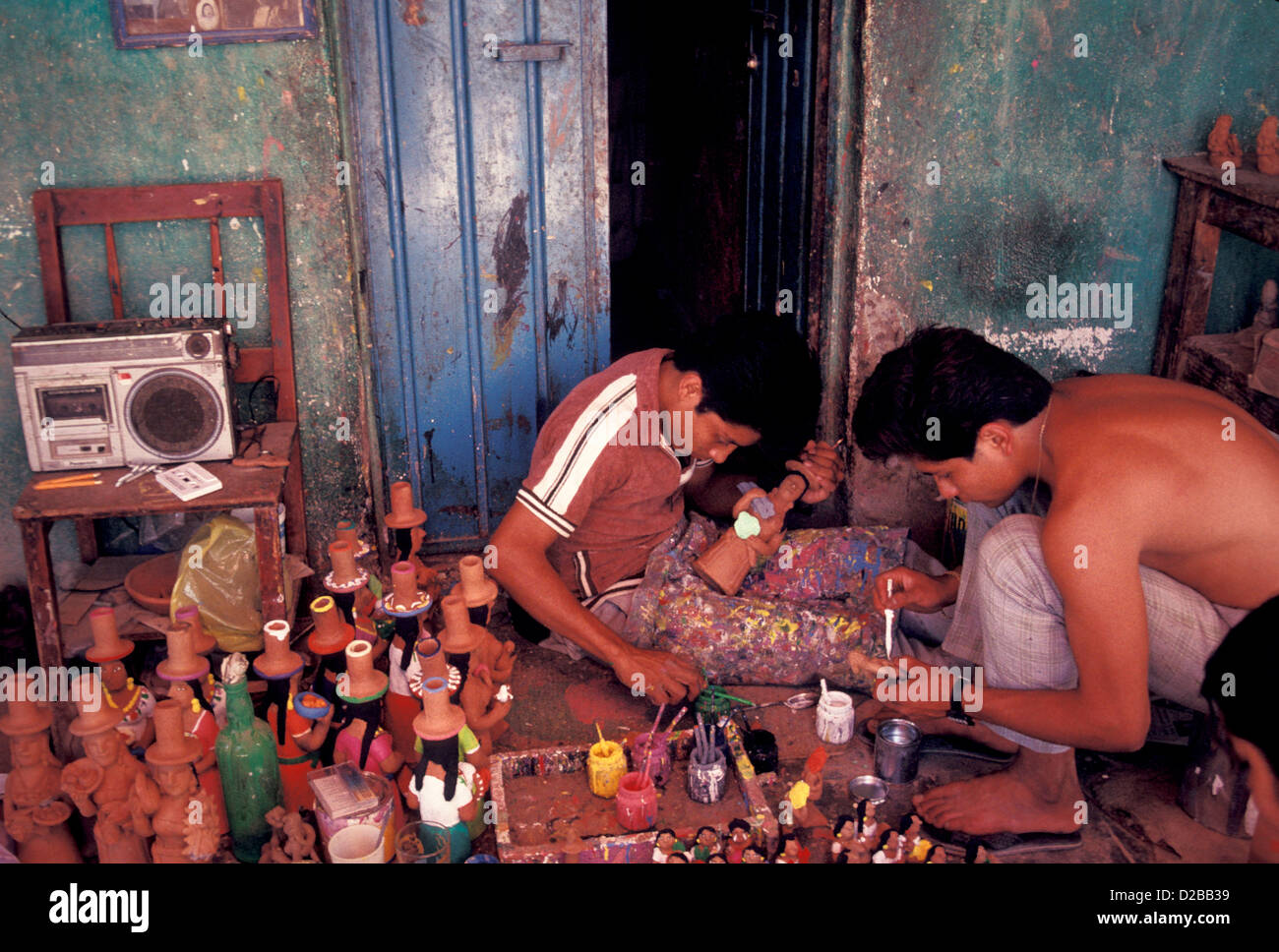 Costa Rica, 2 Men Painting Figurines Outside In Front Of Doorway Listening To Radio - Stock Image