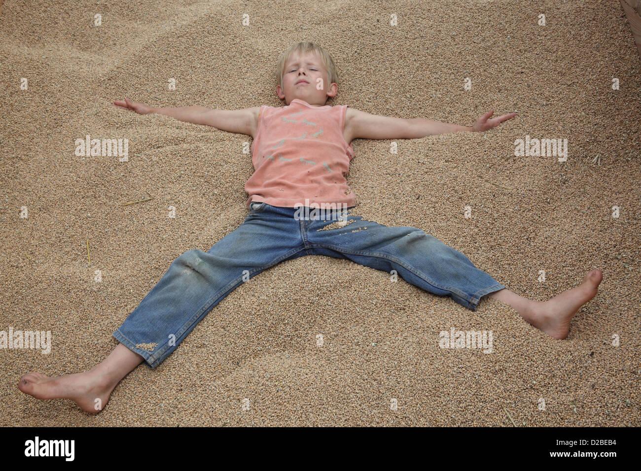 Resplendent village, Germany, boy lies on Weizenkoernern Stock Photo