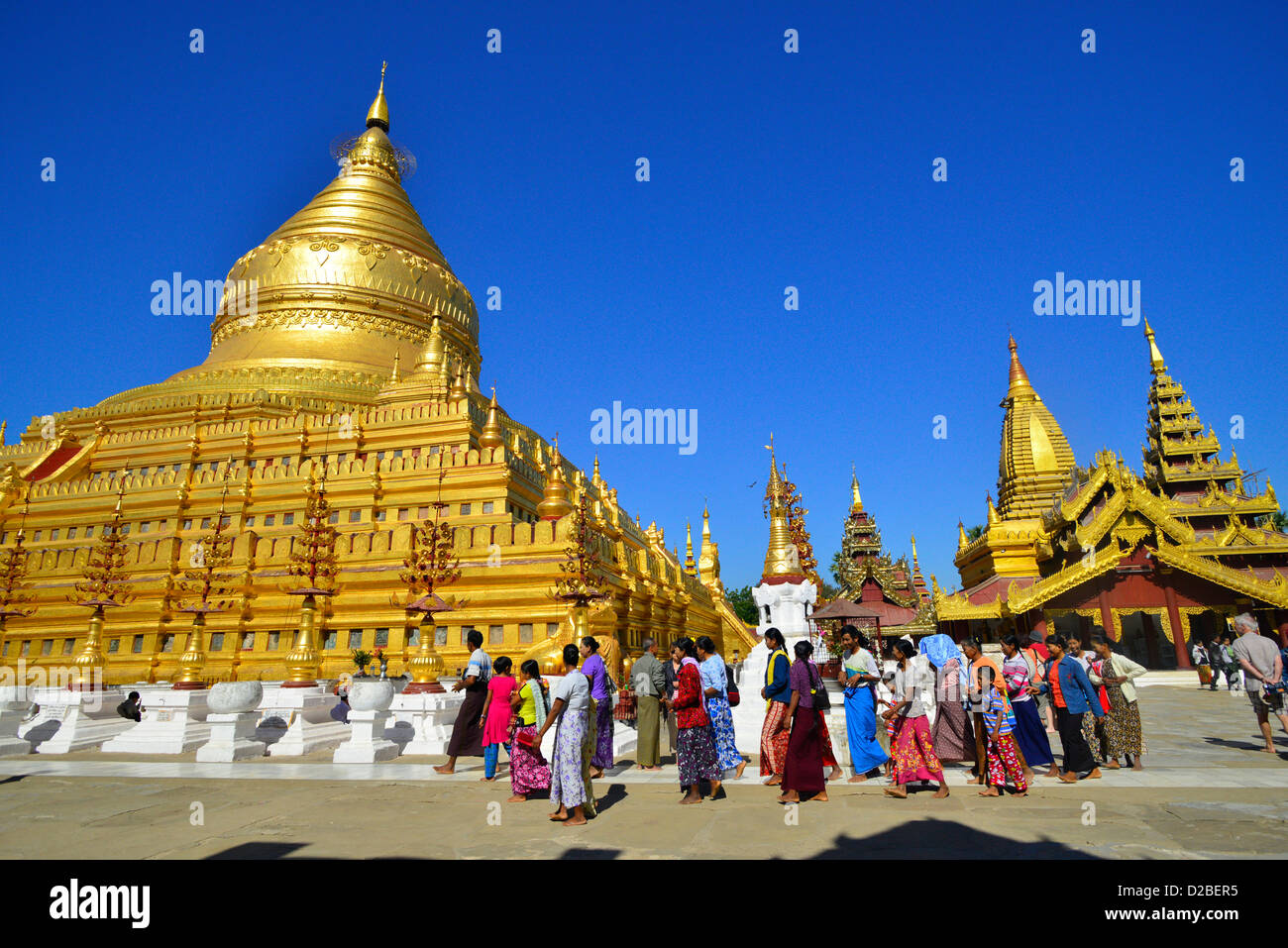 Pilgrims walk around the Shwezigon Paya Golden Pagoda in Paya, Bagan, Myanmar. Stock Photo