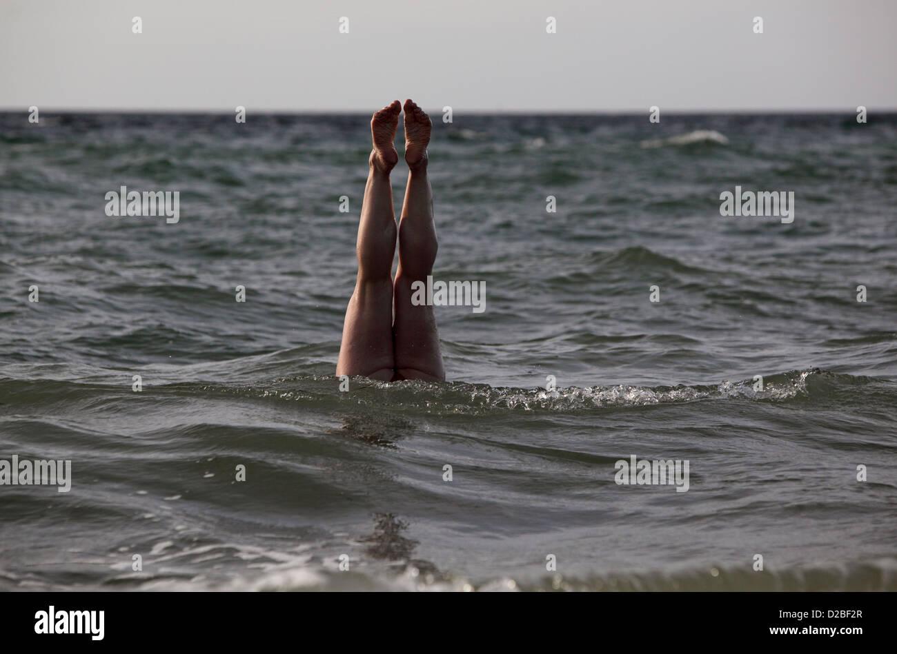 Kägsdorf, Germany, human legs look out of the sea - Stock Image