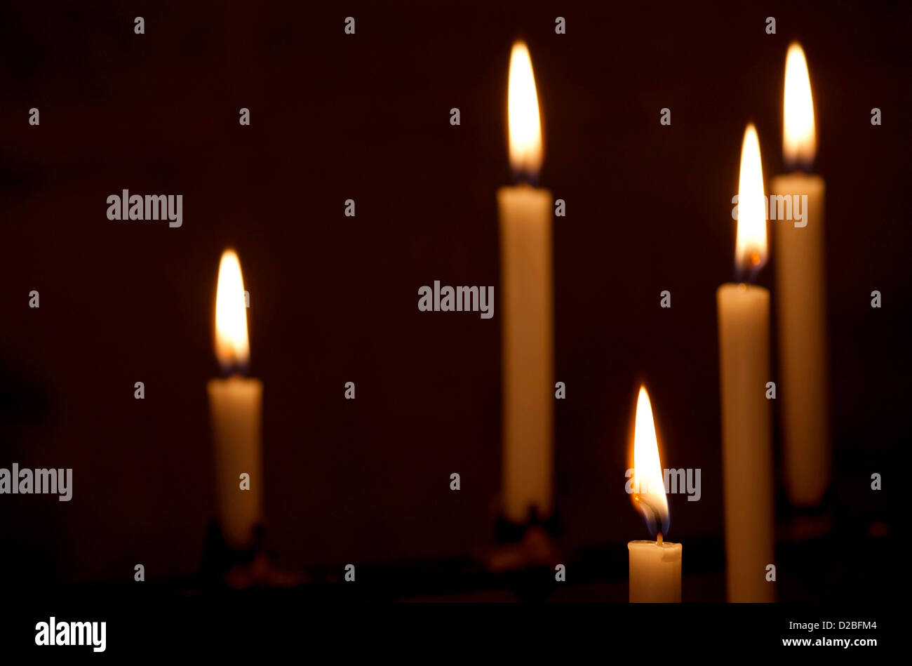 Closeup of five white prayer candles all lit, focus on