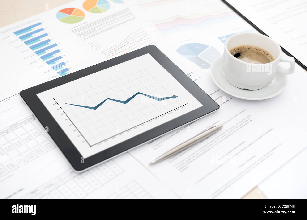 Desktop with bad statistic report on a modern digital tablet, some papers with charts and graphs and with a cup - Stock Image