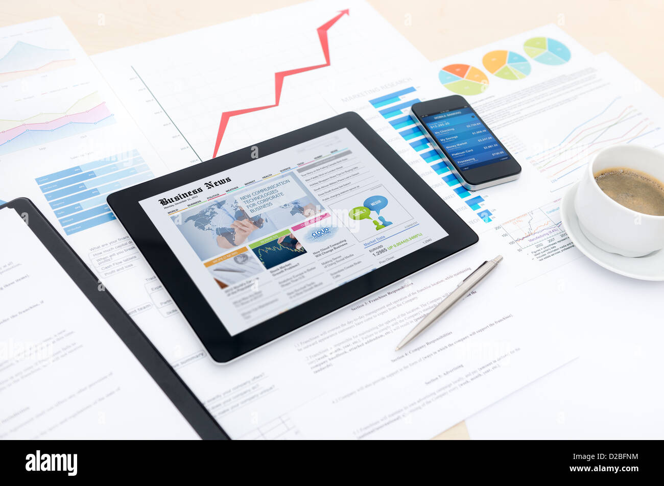 Modern business workplace with business news website on a digital tablet and some charts and graphs on a desktop Stock Photo
