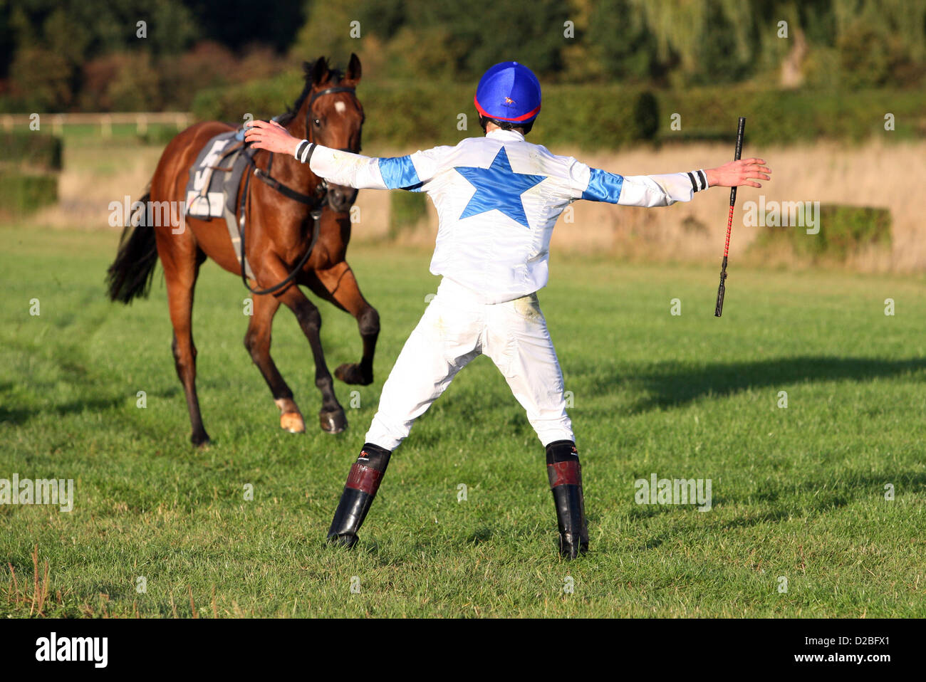 Hannover, Germany, jockey tries to stop his riderless horse - Stock Image
