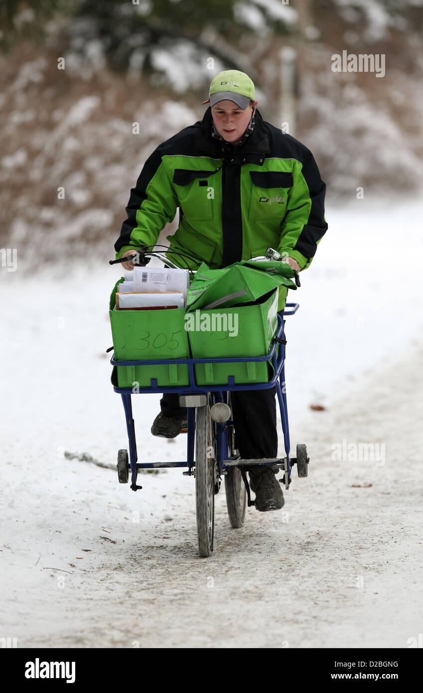 Berlin, Germany, the postman PIN AG is proceeding bike along a snowy sidewalk Stock Photo