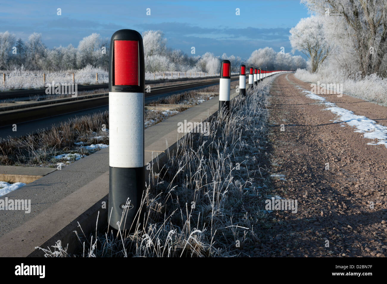 Bollards along edge of the guided busway or bus track between St Ives and Cambridge Cambridgeshire UK on a cold Stock Photo