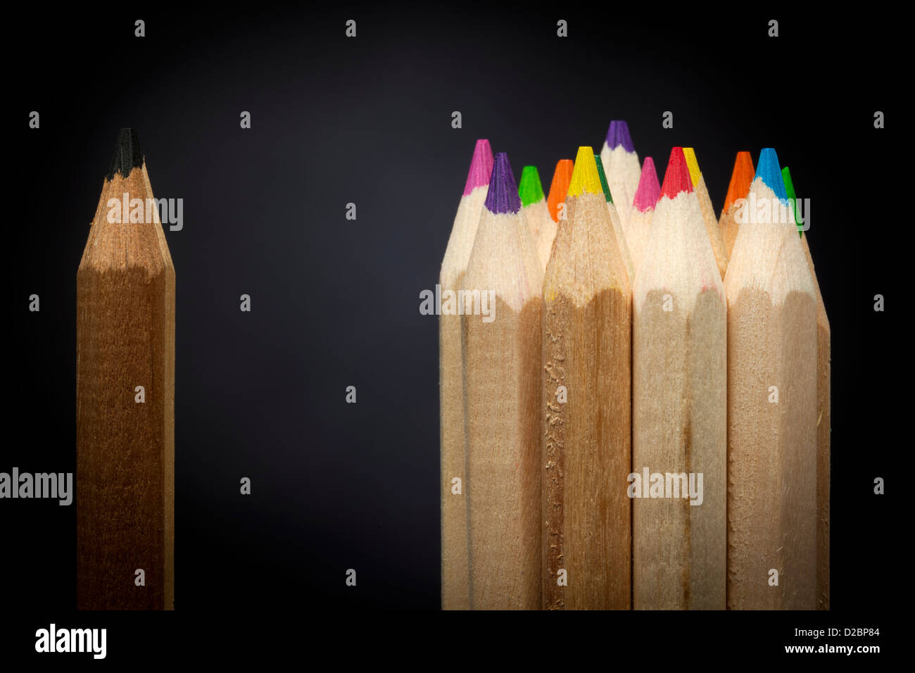 Isolation concept - black pencil standing apart from group of colored pencils - Stock Image