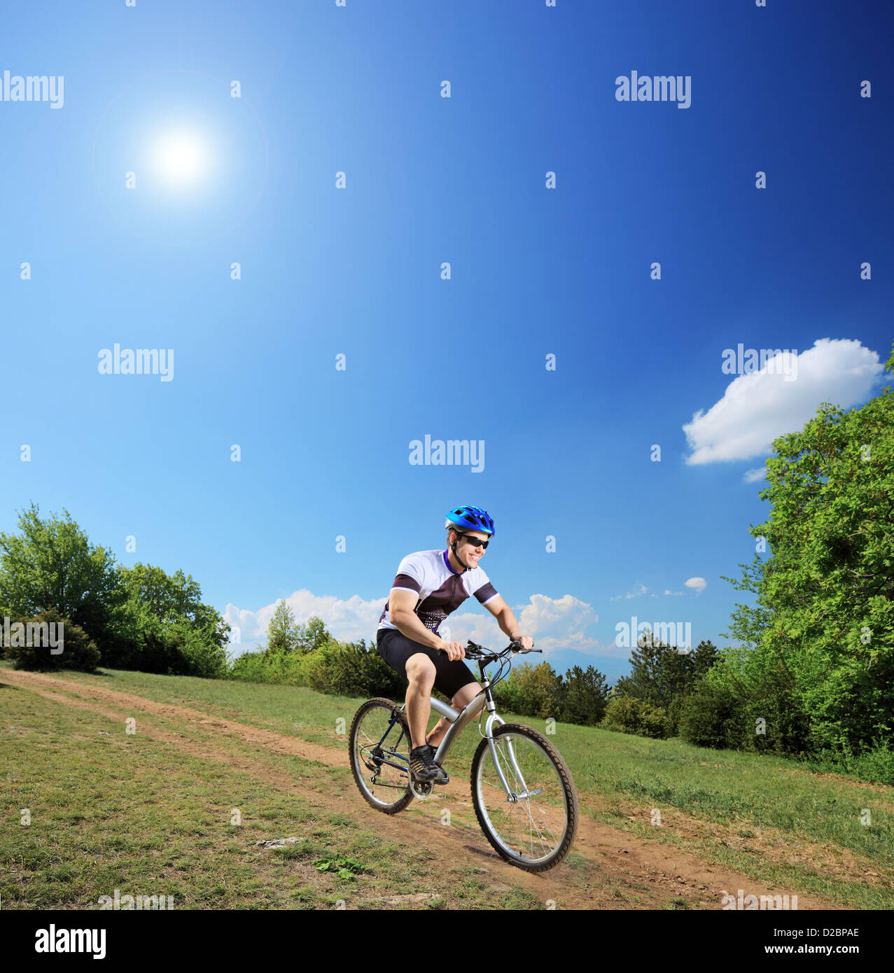 Male bicyclist riding a mountain bike down hill on a sunny day, shot with a tilt and shift lens - Stock Image