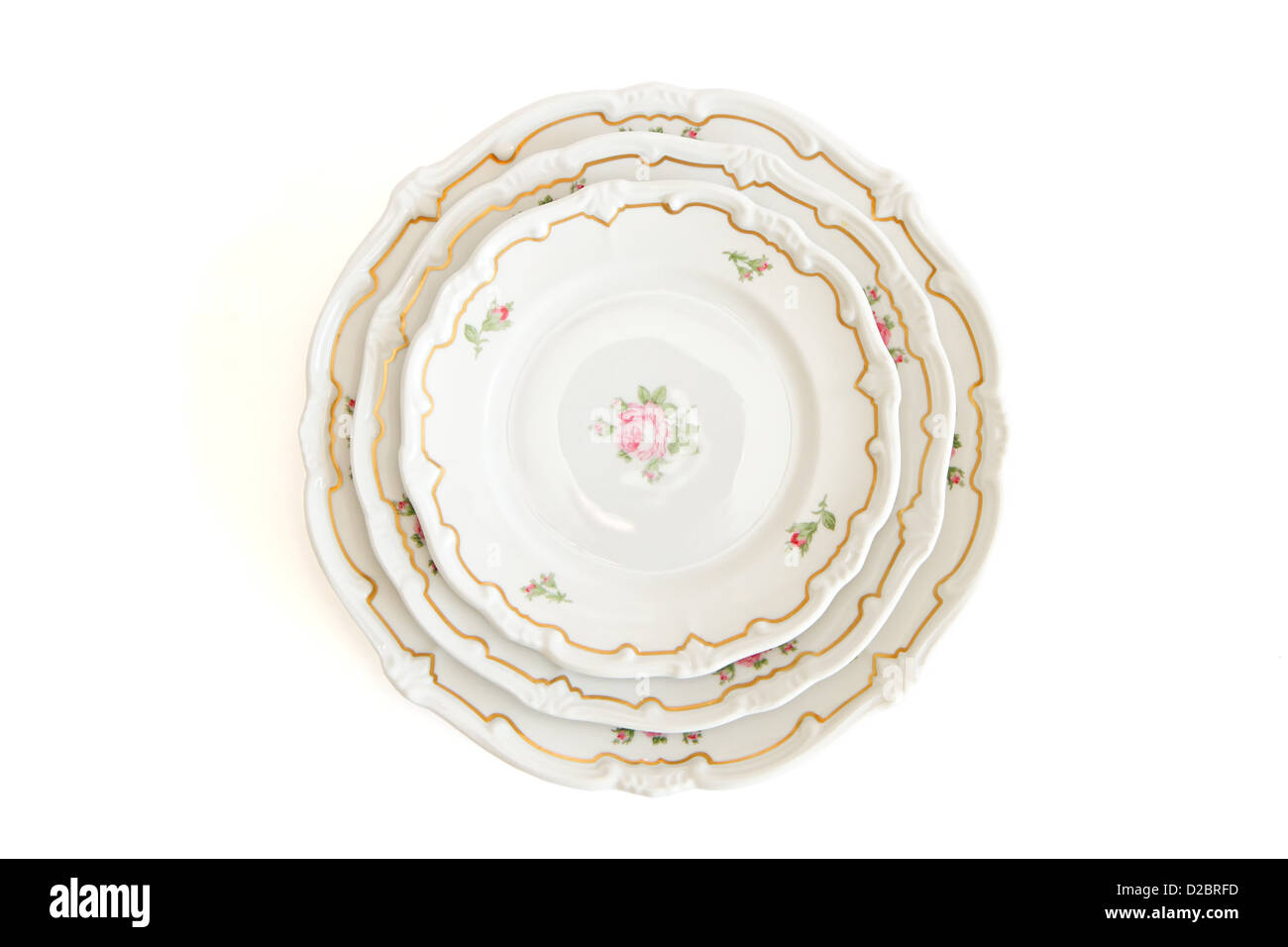 Stack of three white dinner plates and saucers with flowers and wavy rim top view isolated - Stock Image